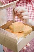 Woman holding box of cornbread (pieces)