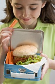 Girl holding lunch box containing burger & carrots
