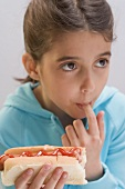 Little girl eating hot dog with ketchup