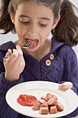 Little girl eating frankfurters with ketchup