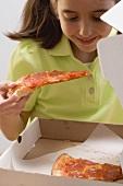 Little girl holding slice of pizza over pizza box