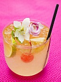 Drink with lime, cocktail cherry and exotic flowers