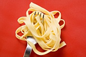 Ribbon pasta wrapped around fork on red background