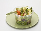 Avocado salad with sprouts in plastic container