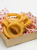 Deep-fried onion rings with ketchup in a cardboard box