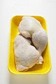 Two fresh chicken legs in polystyrene tray