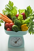 Fresh vegetables and parsley on kitchen scales