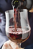 Person pouring red wine into a glass