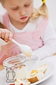Little girl trickling honey onto bread and butter