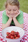 Girl looking at strawberries in colander