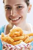 Young woman holding deep-fried onion rings in paper dish