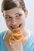 Junge Frau beisst in frittierten Zwiebelring auf Zeigefinger