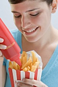 Young woman squeezing ketchup out of bottle onto chips