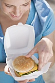 Young woman taking cheeseburger out of polystyrene box