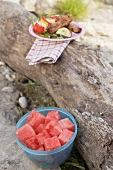 Plate of grilled food on tree trunk, bowl of diced watermelon