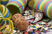 Sparkling wine cork, confetti and paper streamers
