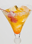 Tequila Sunrise with ice cubes and cocktail cherries