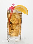 Rum drink with ice cubes and orange wedge