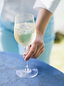 Woman reaching for glass of white wine with ice cubes on table