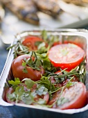 Tomatoes with fresh herbs in aluminium dish, ready for grilling