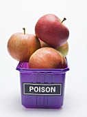 Red apples in a plastic punnet with a 'POISON' label