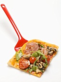 Slice of pizza topped with ham, tomatoes, mushrooms, rocket