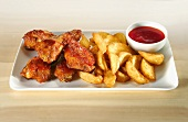 Chicken wings with potato wedges and ketchup