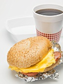 Sesame bagel with scrambled egg, cheese & ham, cup of coffee