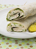 Wraps and gherkin slices on plate