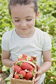 Little girl holding basket of strawberries