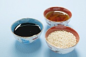 Asian sauces and sesame seeds in small bowls