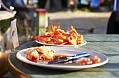 Peeled and unpeeled prawns on plates