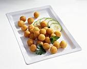 Deep-fried potato balls with sliced cucumber