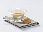 Vanilla cream in glass bowl and two cookies
