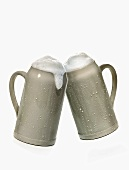 Two mugs of beer clinking together