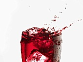 Cranberry juice splashing out of a glass