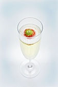 A glass of sparkling wine with strawberry