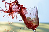 Red wine splashing out of a glass