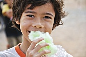 Boy eating green candyfloss