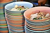 Noodle soup with meat prepared in plastic bowls (Thailand)