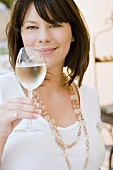 Young woman holding a glass of white wine