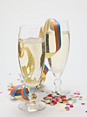 Two glasses of sparkling wine, paper streamer and confetti