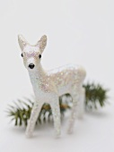 Christmas decoration (deer) in front of sprig of fir