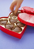 Hand taking chocolate out of heart-shaped box