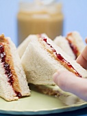 Hand reaching for peanut butter and jelly sandwich