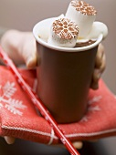 Hand holding beaker of hot chocolate with marshmallows & cream