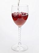 Cranberrydrink mit Wasser aufgiessen