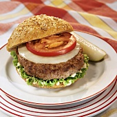 Cheeseburger with Tomato on Whole Grain Roll; Pickle
