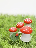 Lucky charms (fly agaric mushrooms, 4-leaf clover) in grass