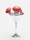 Marzipan fly agaric mushrooms in cocktail glass